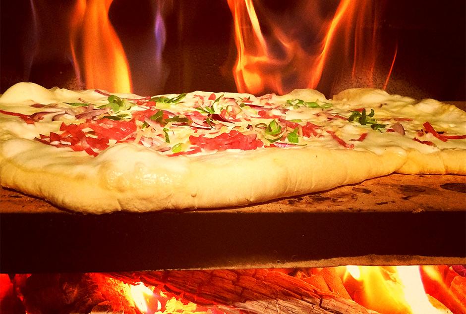 Pizzabacken mit dem Pizzastein auf Feuerschale und Grill